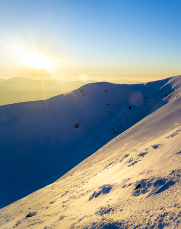 Winter sunset in the mountains. Direct sunlight. Sun beam. Light reflected from the snow. Steep slope. Clear blue sky. Deep shadows. Ukraine