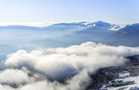 Winter landscape of a blue mountains and fluffy clouds in the valley. Carpathian Ukraine
