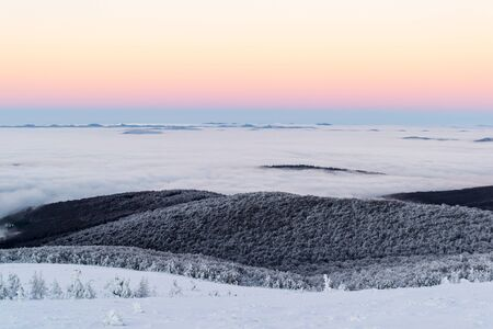 Scenic winter landscape above the clouds. The sky is clear. After dusk. Zdjęcie Seryjne