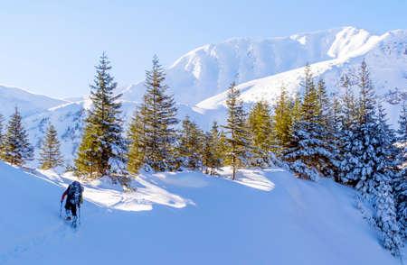 Winter mountain trekking. The man hikes on footpath in the snow. Zdjęcie Seryjne