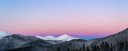 Winter morning panoramic view of snowy mountain peaks. Dawn.