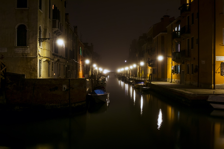Quiet canal at night in Venice. Warm light of the street lights illuminates the street and reflected in waterways. Private boats are parked along the canal. The bridge silhouette is visible at the end of the waterway