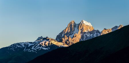 Morning view of Ushba mountain on the background of a clean blue sky. Morning sun illuminates the rock wall. Summer in Georgia. Svaneti. Caucasus.