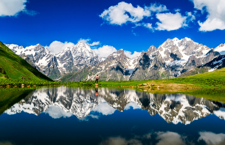 Mirror Lake on the background of snowy mountains. Blue sky with white clouds. Human silhouette and mirror image of nature in the lake. Summer. Georgia. Svaneti, Mestia