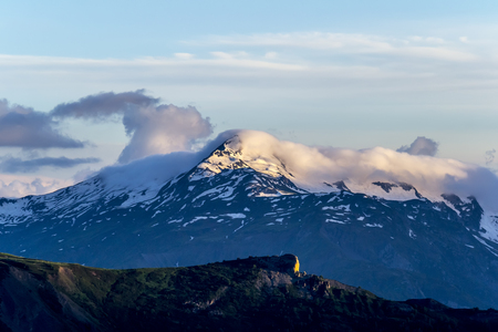 Mountain landscape. Peak with snow in evening sunlight and a cloud above. Summer in Georgia.
