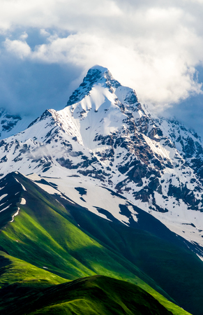 Images of high and snow-covered mountain peak. White clouds are visible behind the lighted mountain top. Summer in Caucasian Georgia. Vertical orientation photo.