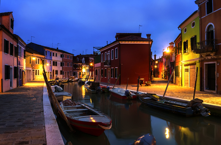Quiet evening cityscape of Burano island in Venice. Rainbow colors of small cottages. Dark blue sky. Small boats are parked along the water canal.