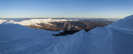 Winter in the Ukrainian Carpathians. Snowy mountain ridge. Traces of wind and frost in the snow. Wide panorama