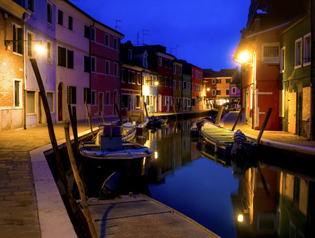 Quiet evening cityscape of Burano island in Venice. Colored buildings are illuminated by street lights on the background of the water channel and the small bridge.