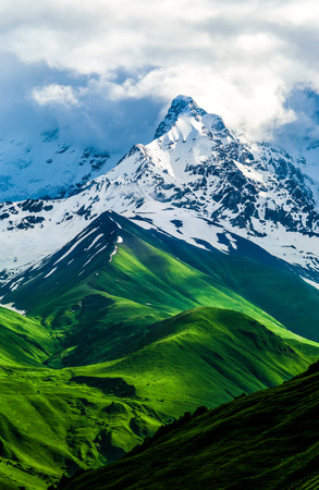 Beautiful view of the snowy mountain peak. Green fields and hills changes to snow. Storm white clouds are visible behind the lighted mountain top. Summer in Georgia. Caucasus. Svaneti, Ushguli. Vertical orientation photo.
