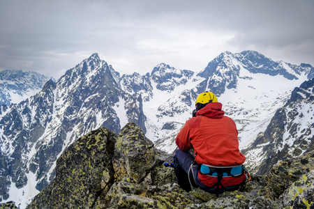 A climber looking at the snow-capped mountains sitting on a rock. High Tatras, Slovakia