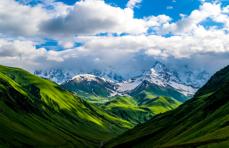 Beautiful landscape of mountains and valleys. Green fields and hills leading to snow-covered mountains. White clouds on the mountain range. Summer in Caucasian. Georgia. Zdjęcie Seryjne