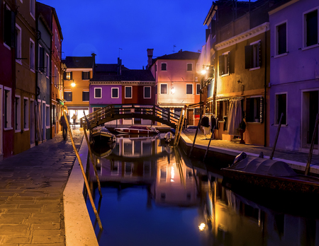 Evening cityscape of Burano island in Venice. Colored buildings and a small bridge illuminated by street lights, reflected in a water canal. Zdjęcie Seryjne