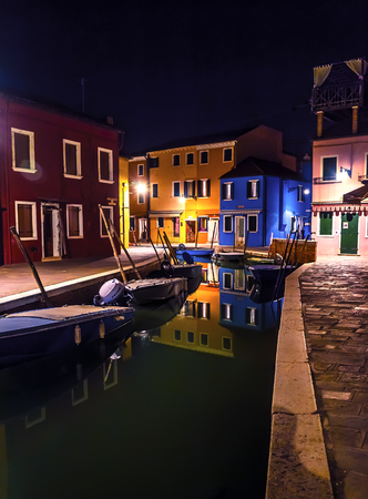 Beautiful night cityscape. Colored buildings are illuminated by street lights reflected in a water canal. Boats are parked there. Venice, Burano island.