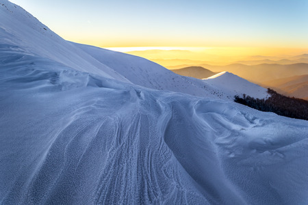 Winter evening in the Ukrainian Carpathians. Gentle sun rays enlighten snowy mountain ridge. Traces of wind and frost in the snow. Mountains on the background is blurred.