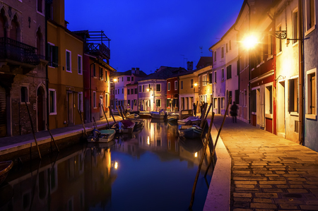 Beautiful evening cityscape of Burano island in Venice. Colored buildings are illuminated by street lights reflected in a water canal. Boats are parked there.