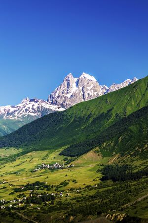Ushba mountain on the background of a clean blue sky. In the valley there are small villages. Summer in Georgia. Svaneti. Zdjęcie Seryjne