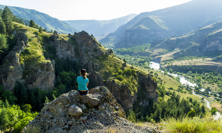 Girl sitting on a rock looking at the view. Against the background of sharp rocks, hills, valley. Clear sky, green hills, steep cliffs, wide river - the extraordinary nature of Georgia.