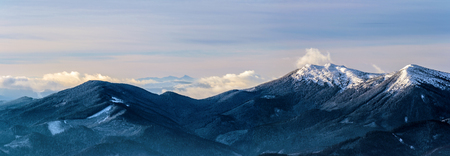 Distant peaks in morning light. Blue mountain ranges covered with trees. Ukrainian Carpathian Mountains