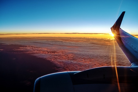 Sunset from a plain. View through the window of an aircraft. Wing of the plane above clouds.