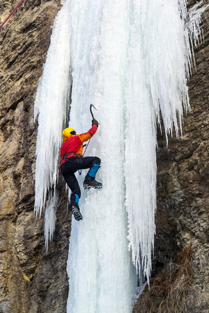 Extreme ice climbing. Man climbing the frozen waterfall using ice axes and crampons. Reklamní fotografie