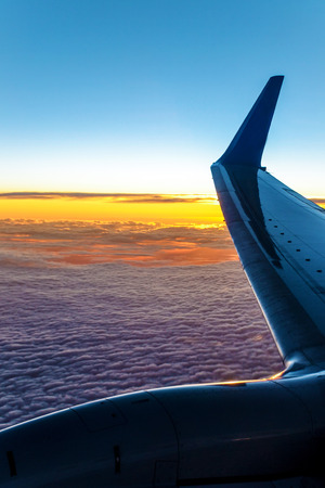 Sky from a plain. View through the window of an aircraft. Wing of the plane above clouds. Sunset colors. Zdjęcie Seryjne