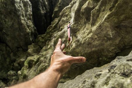 The climber's hand reaches the carbine. Rock climbing