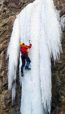 Man climbing the frozen waterfall using ice axes and crampons. Extreme ice climbing. Winter Zdjęcie Seryjne