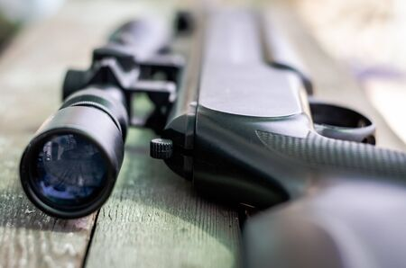 Sniper rifle lies on a wooden background. Optical sight close-up. The concept of hunting