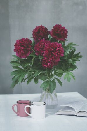 A vase with red peonies, cups of tea and a book on the table. Greeting card for the holidays of love.