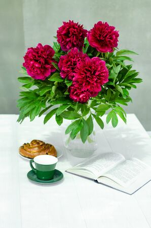 Spring still life. Vase with flowers, a cup of coffee, a book and a fresh bun on the table