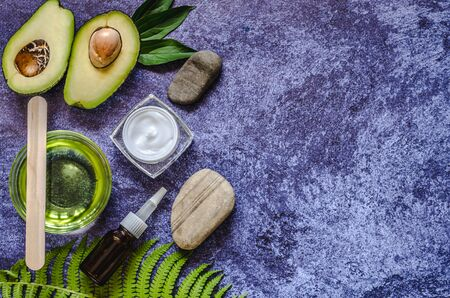 Two halves of avocado, avocado oil, fern leaf and massage stone. Natural Organic Product Beauty Concept