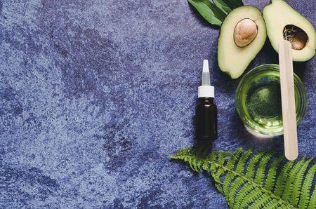 Beauty concept of natural organic product. A dark bottle for oil, a bowl with avocado oil, a leaf of fern and two halves of avocado against a dark background. Beauty background