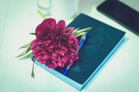 Peony lying on notepad. Closed notebook, pen, cup of tea and peony flower on a white wooden background. Layout for your design Zdjęcie Seryjne