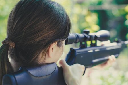 A girl looks into the scope of a sniper rifle. Back view. Weapons in the hands of a girl. Hunting Woman with guns