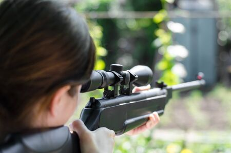 Girl sniper holds a gun in his hands. The hunter is looking into the optical sight from a rear view. Pneumatic gun. looks into the scope of a sniper rifle 写真素材