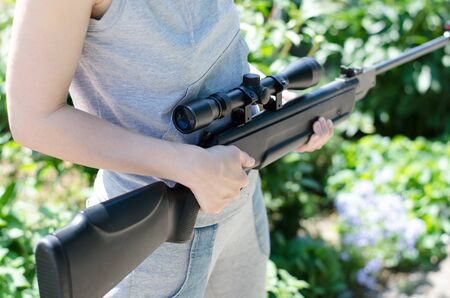 The girl is holding a pneumatic sniper rifle. Black sniper rifle with a telescopic sight. Hunter girl. Woman with guns 写真素材