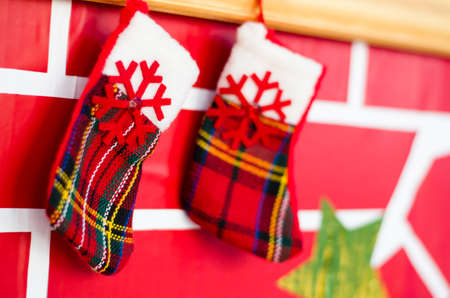 Christmas socks for gifts hang on the decorative fireplace. Greeting card. 免版税图像