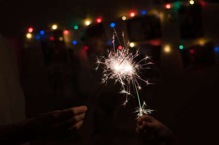 People are holding a sparkler in their hands on a blurred background of garlands. Christmas vacations and holidays concept. 免版税图像