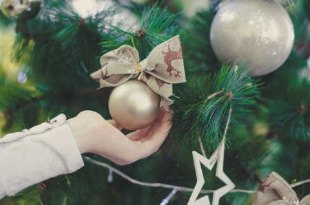 A childs hand touches the Christmas toy. Decorations on the tree, selective focus. Christmas holidays concept