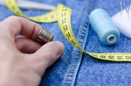 A man's hand holds a thimble and a pin. Cutting and sewing supplies are on the denim skirt. Centimeter, thread and pins. Standard-Bild