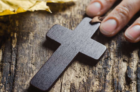 Wooden Christian cross and female hand illuminated by a ray of sun