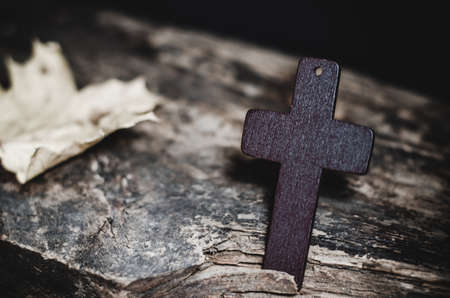 Wooden Christian cross on a wooden table. Religious concept