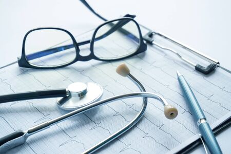cardiogram with stethoscope, pen, magnifier, pills and glasses lay on a table Archivio Fotografico