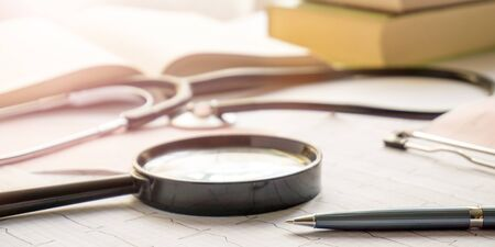 stethoscope, magnifier, pen and books lay on cardiograms on table