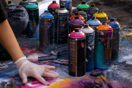 girl street artist in gloves paints with spray cans of paint on a piece of paper. multicolored cans of paint stand around. copy space