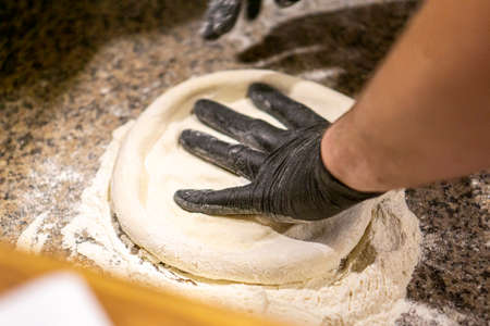 pizza chef kneads pizza dough in gloves. copy space 免版税图像