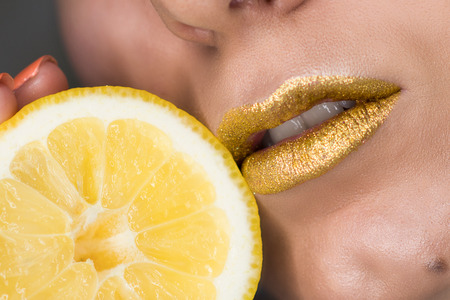 Beautiful closeup with female lips with gold color makeup and lemon slice. Glitter cosmetics