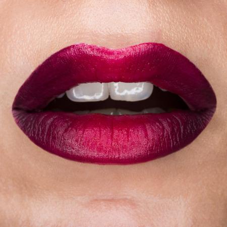 Nahaufnahmemakro schöne Lippen mit rotem Mattlippenstift. Roter Farbverlauf, weiße Zähne und offener Mund. Lippenkunst