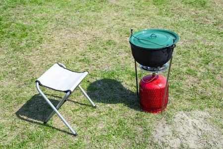 Red portable gas-stove with cauldron on it near chair on green grass. Coocking outside on camping or fishing Banco de Imagens
